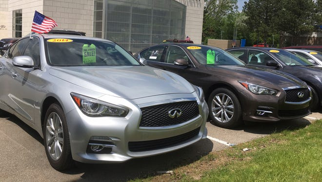 Infiniti Q50 luxury sedans await buyers at a dealership in Novi.