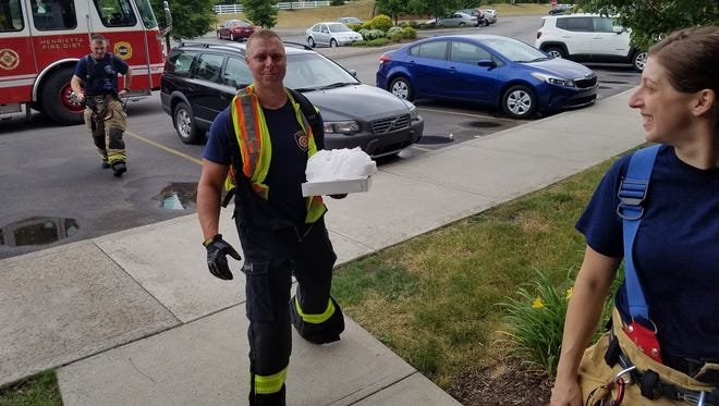 Henrietta Firefighters make a pizza delivery after the pizza delivery guy was in an accident. Jeremy Meisenzahl carries out the order.