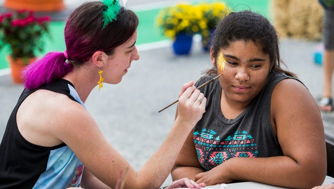 Ten-year-old Giovanna DelleDonne gets her face painted by Susanna Bucci along Union Street as part of the Better Block Project in Wilmington on Monday evening.
