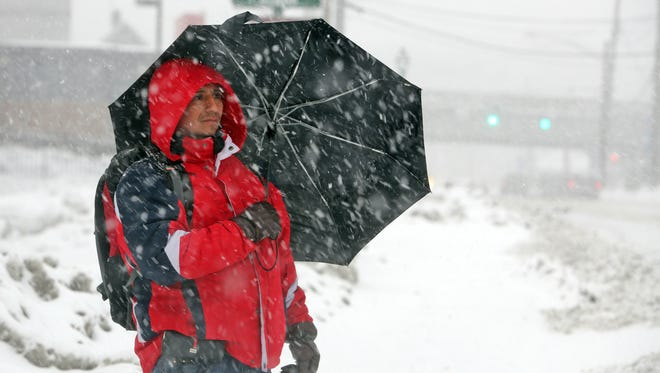 A Yonkers resident uses an umbrella for protection against the heavy snow as he waits for a bus in Elmsford.