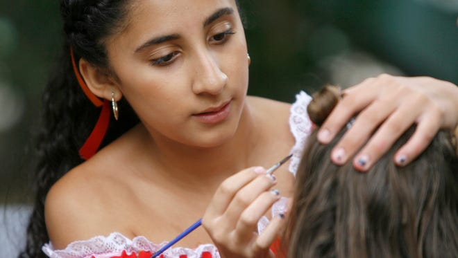 Karla Rubio paints faces during the Ojai Valley Mexican Fiesta.