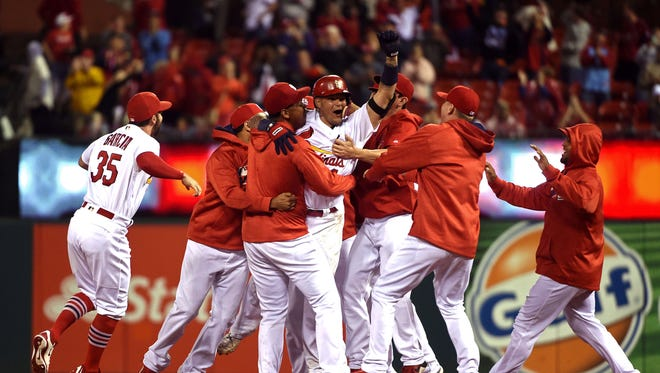 Yadier Molina celebrates after hitting a walk off double to beat the Reds.