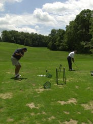 Golfers practicing their swings at the Elmwood Country