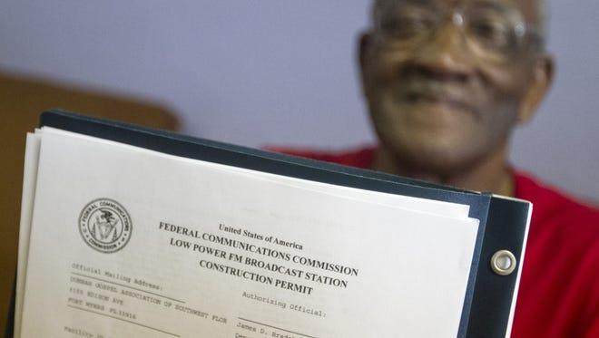 The Rev. Jessie Denson, president of the Dunbar Gospel Association, shows the FCC permit for STAR-FM last year.