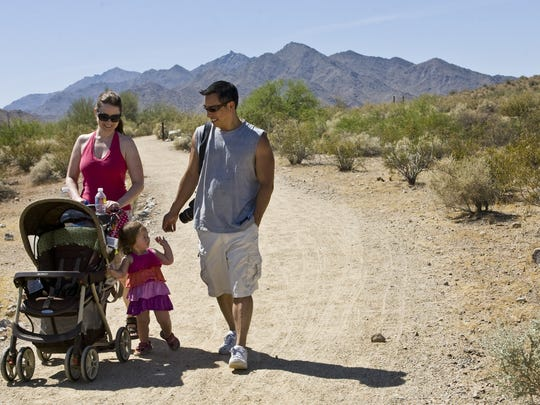 Jenniffer Watson, right, of Goodyear, walks with Hana Agcaoili, 2, and her father, Jim Agcaoili both of Foster City, CA at Estrella Mountain Regional Park in Goodyear on Friday, June 4, 2010.
