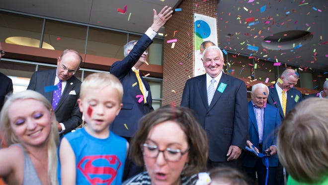 A grinning Tom Golisano is surrounded by confetti and miracle kids during a ribbon cutting ceremony at the new Golisano Children's Hospital on Wednesday, May 27, 2015.