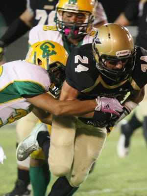 Xavier's Daniel Stabile tries to pull away from two Coachella defenders on a run as Coachella Valley High takes on Xavier Prep in football in Palm Desert, Friday, October 17, 2014.
