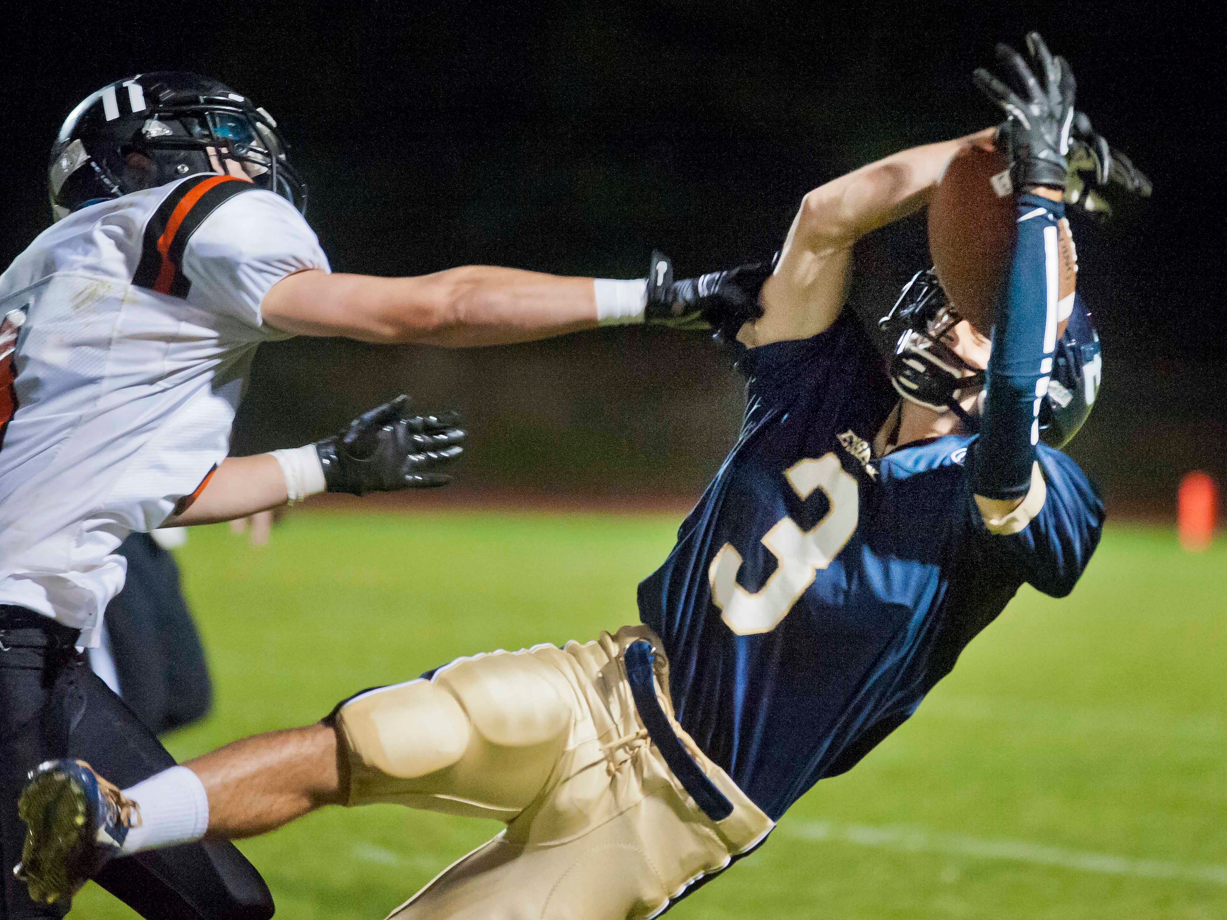 Essex's Matthew Olsen (right) can't hold onto a pass under pressure from Middlebury's Connor Quinn in Essex Junction during Week 1 of the high school football season.