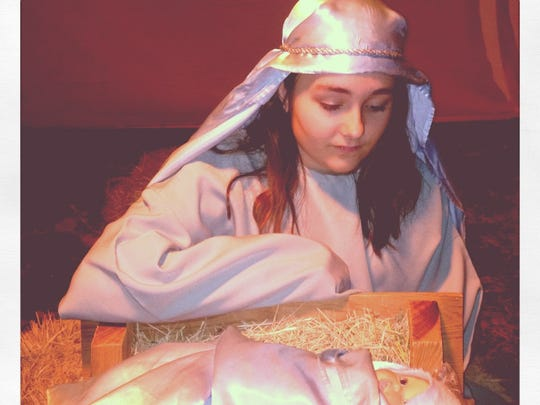 Matty Hohhertz, as Mary, beside baby Jesus in the 2013 living nativity presented by Our Savior Lutheran Church.