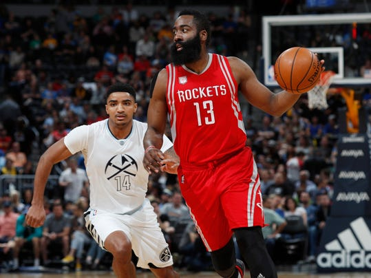 Houston Rockets guard James Harden, front, looks to pass the ball as Denver Nuggets guard Gary Harris pursues in the first half of an NBA basketball game Saturday, March 18, 2017, in Denver. (AP Photo/David Zalubowski)