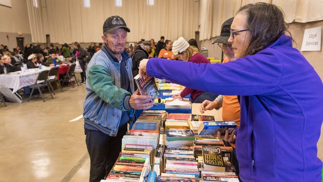 Volunteer Kathryn Hall, right, helps Mark Eaker find books of interest during Project Homeless Connect at Visalia Rescue Mission on Thursday, January 25, 2018.