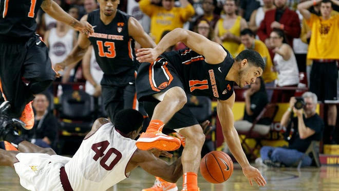 Oregon State's Malcolm Duvivier (11) and Arizona State's Shaquielle McKissic (40) reach for a loose ball during the first half of an NCAA college basketball game, Wednesday, Jan. 28, 2015, in Tempe, Ariz.