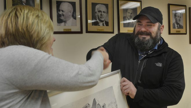 Longtime Fanwood Historic Preservation Commission chairman Adam Kois, right, accepts a handshake and a framed print of the borough's historic north side train station from Mayor Colleen Mahr at a borough council meeting Tuesday night, Feb. 16, in Fanwood. Kois was recognized as the borough's volunteer of the month by the Mayor and Council.