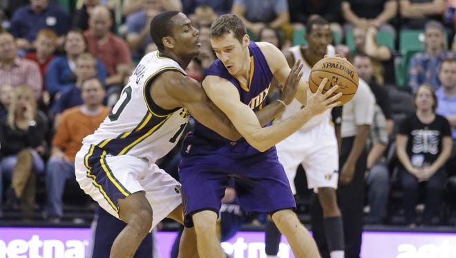The Utah Jazz's Alec Burks (left) defends the Phoenix Suns' Goran Dragic during the fourth quarter of a preseason basketball game on Friday, Oct. 24, 2014, in Salt Lake City. The Suns open their regular season on Wednesday night.