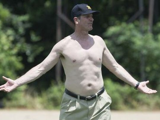 Michigan coach Jim Harbaugh goes shirtless during the football camp in Prattville on Friday.