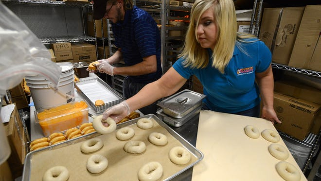 Cameron Stapleton, left, vice president of operations, prepares bagels, as Drew Barnes, ices donuts on the grand opening of Dunkin Donuts in October 2014. The store will now sell Baskin Robbins ice cream.