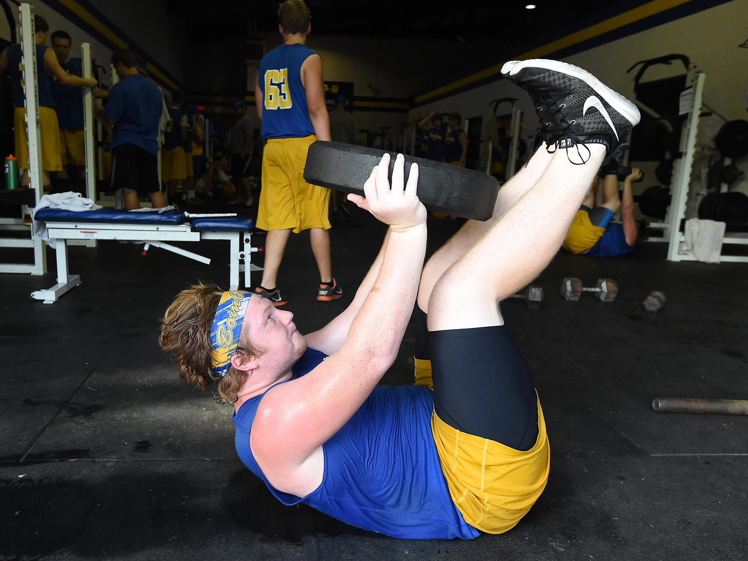 Bomber football player Austin Gamblin lifts weights Tuesday during a voluntary workout. The team hits the weight room several times a week.