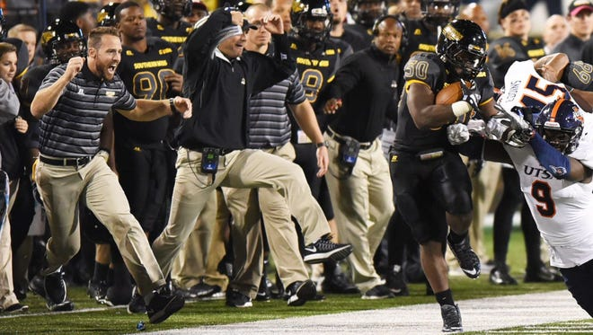 Southern Miss strength and conditioning coach Zac Woodfin, left, cheers on running back Jalen Richard, right, during a game earlier this season.