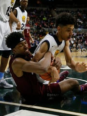 Detroit Western International's Gerald Blacksheer, left, and Saginaw Arthur Hill's Brian Bowen struggle for a loose ball in the MHSAA boys basketball Class A final on March 28, 2015.