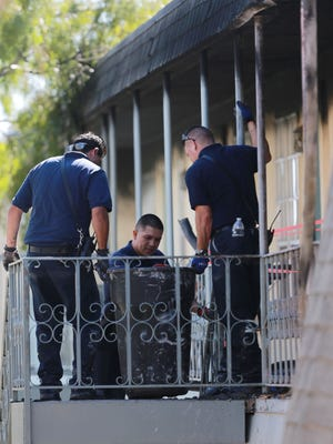 El Paso firefighters carry a container of burnt debris from an apartment at the Las Casitas complex Monday.