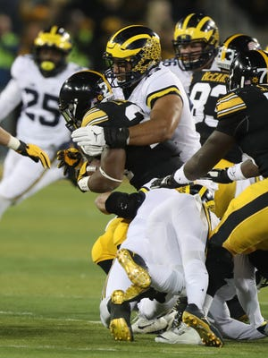 Michigan's Chris Wormley tackles Iowa's LeShun Daniels Jr. during first half Saturday in Iowa City, Iowa.