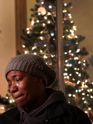 Natalie DuBose weeps outside her Natalie's Cakes and More bakery after vandals broke one of two large windows during rioting in Ferguson, Mo.