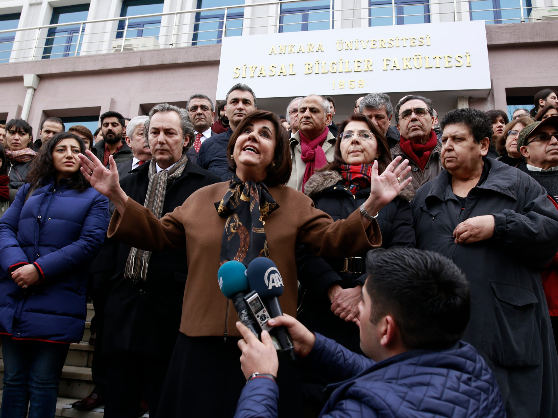 A woman gestures as people protest outside the Ankara University after Turkey's government sacked nearly 4,500 more state employees, including academicians, as it appeared to press ahead with a purge of people with suspected links to a U.S.-based cleric accused of orchestrating a failed military coup, in Ankara, Turkey, Wednesday, Feb. 8, 2017. Turkey declared a state of emergency following the failed July 15 attempt and embarked on a clamp down on Fethullah Gulen's movement, purging more than 100,000 of his followers who are accused of infiltrated the military, police and civil service.
