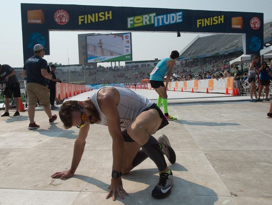 A runner recovers after crossing the finish line at