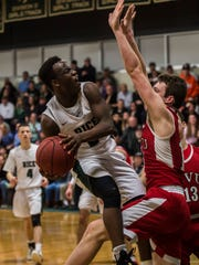 Driving to the basket, Rice #2 Michel Ndayishimiyeg draws the foul that would ultimately win the game, dropping one free throw to make it 62-61 over CVU during their semi-final boys basketball match up at Rice in South Burlington on Friday night, March 9, 2018.