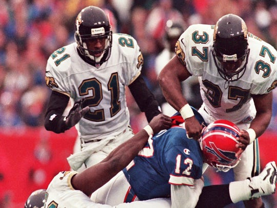 Jim Kelly gets hit hard during his final game, a playoff loss to the Jacksonville Jaguars on Dec. 28, 1996.