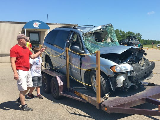 Attendees of Traffic Safety Day look at a van that was involved in an accident caused by distracted driving. Two of the van's passengers eventually died from their injuries.  The display was at the Minnesota Highway Safety and Research Center in St. Cloud on Saturday, July 22, 2017.