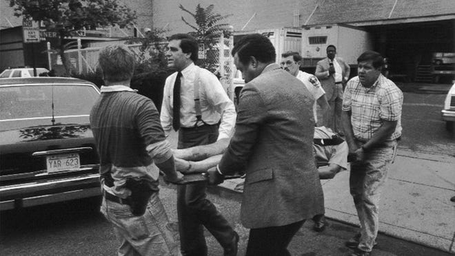 Louisville Mayor Jerry Abramson, white shirt and suspenders, helps carry the wounded from the Standard Gravure shooting scene. By Gary S. Chapman, The Courier-Journal. Sept. 14, 1989.