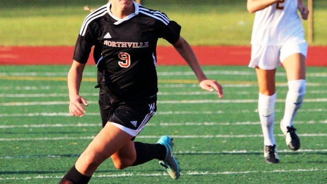 Northville's Sydney Schembri pushes the ball up field with Mercy's Kacey Cerretani trailing the play.