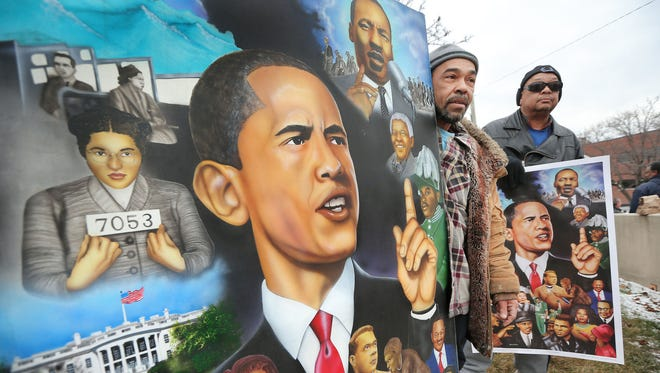 Artist Terry Wilson of Indianapolis, left, holds a painting he created as he and Kevin Varnado, also of Indianapolis, show their support for President Barack Obama at the intersection of 29th and Meridian streets, before his speech at Ivy Tech Community College in Indianapolis on Friday, Feb. 6, 2015.