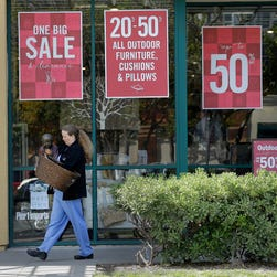 A woman leaves a department store after shopping in Emeryville, Calif.
