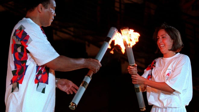 American swimmer Janet Evans passes the Olympic flame to Muhammad Ali during the 1996 Summer Olympic Games Opening Ceremony in Atlanta.