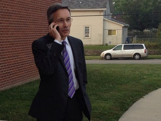 Richmond Community Schools Superintendent Allen Bourff talks on the phone as he waits for buses to arrive at Fairview Elementary School on the first day of school Wednesday, Aug. 6, 2014. Bourff said he would make the rounds of all schools during the day.