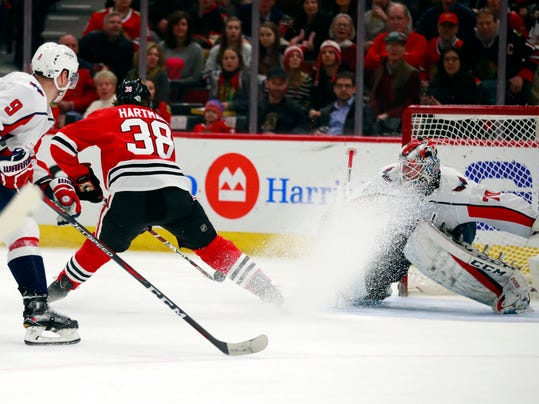 Chicago Blackhawks left wing Ryan Hartman (38) backhands a goal past Washington Capitals goaltender Braden Holtby during the second period of an NHL hockey game Saturday, Feb. 17, 2018, in Chicago. (AP Photo/Jeff Haynes)