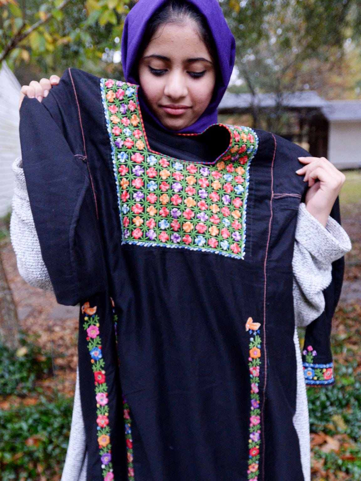 Noor Al-Shaier, an exchange student, holds up a traditional