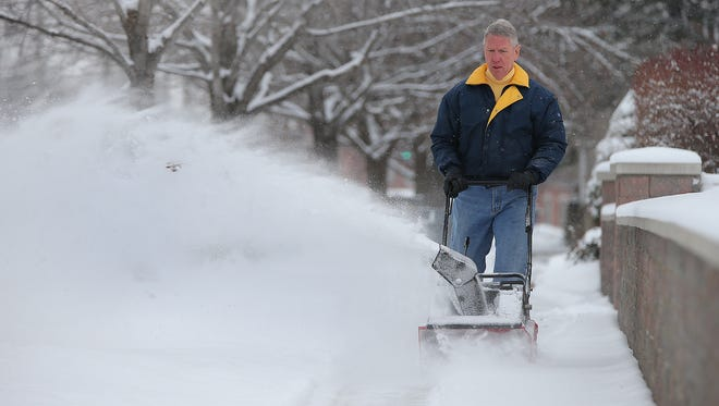Jim Knauer, of Fletcher Pointe condominiums, blows the snow from the sidewalks surrounding property at the corner of Fletcher and South Street Tuesday, January 6, 2015, morning following the overnight snowfall.