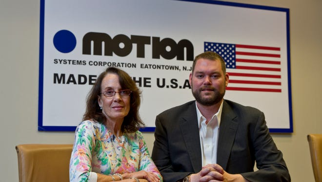 Motion Systems is a family-owned manufacturer of custom electromechanical linear actuators. Controller Kathleen Ryan and CEO Wolf pose in the Eatontown headquarters.