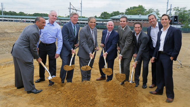 Elected officials and property developers break ground Monday for a photograph during a ceremony for a 227-unit rental property at the Aberdeen-Matawan Train Station, which will offer luxury apartments and retail space in Aberdeen.