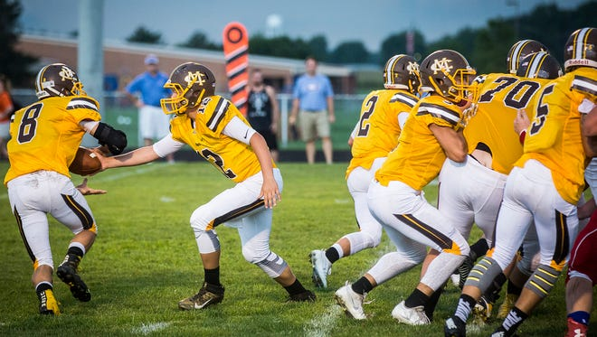 Monroe Central's Casey Conatser makes a hand off to Seth Wilson during their game against Union County at Monroe Central High School Friday, Aug. 26, 2016.