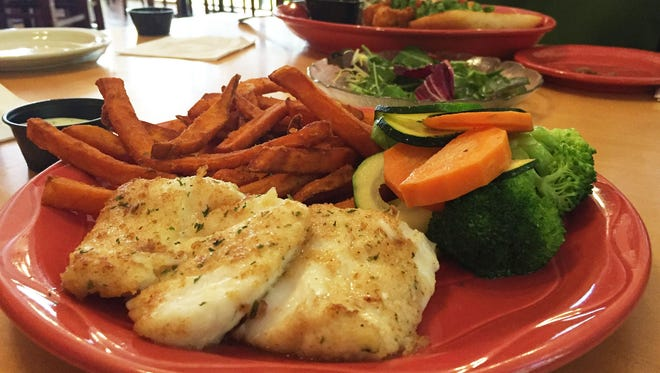 A filet of sautéed grouper with sweet potato fries and vegetables is my first step into the fresh seafood world.