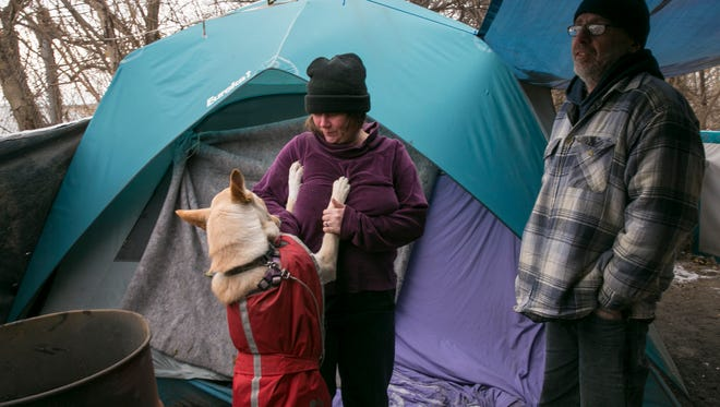 Shannon Aguilera-Martinez (left), hangs out with her dog Sissy and fiance Bobby Young, as they keep warm on a chilly morning near the White River, Indianapolis, Thursday, Dec. 28, 2017. Horizon House runs one of several homeless outreach services that have been active during recent cold temperatures in central Indiana that are expected to bottom out near zero degrees Fahrenheit on New Year's Eve.