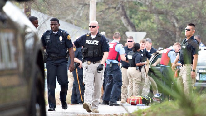 A Montgomery Police officer is walked off the scene as Montgomery Police respond to a shooting scene on Wednesday, Feb. 21, 2018, in Montgomery, Ala. Montgomery Police said an officer was shot with non-life threatening injuries and a potential suspect was killed.