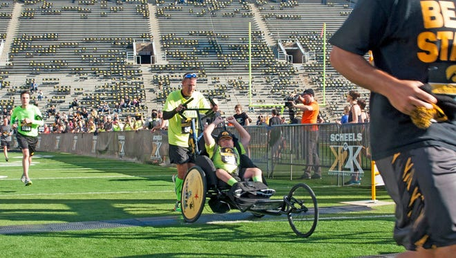 Ryan Hemann, 16, of Osage crosses the finish line with running partner Brad Gentz in last September's Kickoff to Kinnick 5K. Gentz is the boy's mailman and the two are now running partners.