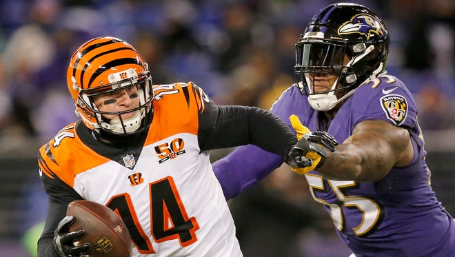 Cincinnati Bengals quarterback Andy Dalton (14) scrambles away from a blitzing Baltimore Ravens outside linebacker Terrell Suggs (55) in the second quarter of the NFL Week 17 game between the Baltimore Ravens and the Cincinnati Bengals at M&T Bank Stadium in Baltimore on Sunday, Dec. 31, 2017. At halftime the Bengals led 17-10.
