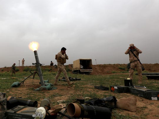 Iraqi soldiers fire mortar shells as they hold a position