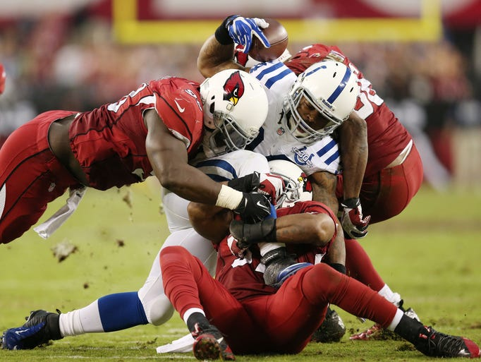 Cardinals defensive players Frostee Rucker, left, Yeremiah Bell, middle and Karlos Dansby stop Colts running back  Trent Richardson during the fourth quarter an NFL game at The University of Phoenix Stadium in Glendale, Az. on Sunday, November 24, 2013. Matt Kryger / The Star